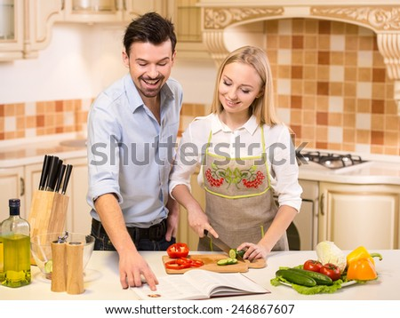 Beautiful, young couple in the kitchen while cooking.