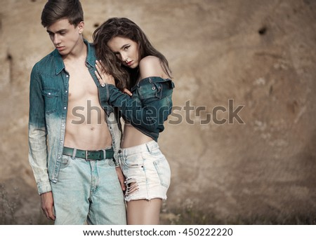 Beautiful young couple in trendy jeans clothes posing outdoor. Casual style. - stock photo