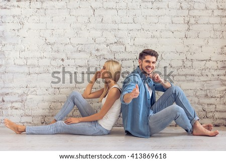 Beautiful young couple is sitting back to back on floor against white brick wall. Man is looking and pointing on camera - stock photo