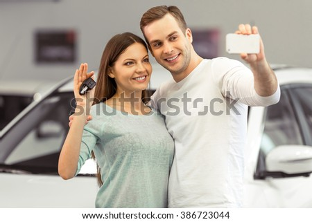 Beautiful young couple is smiling and making a selfie using a smart phone while buying a car in a motor show. Woman is holding keys - stock photo