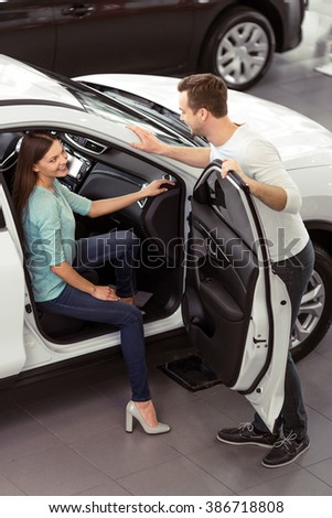 Beautiful young couple is smiling and talking while examining their new car in a motor show. Woman is sitting in a car