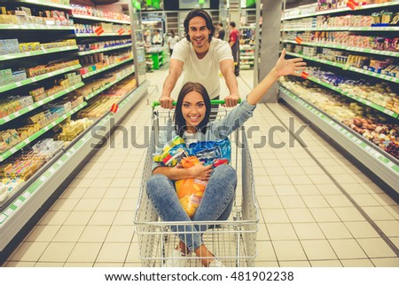 Beautiful young couple is taking fun while choosing food in the supermarket. Father is pushing a shopping cart while his girl is sitting there