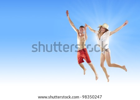 Beautiful young couple jumping on the beach