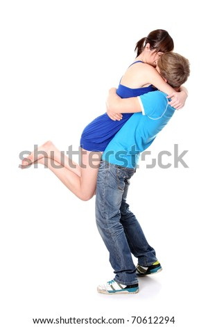 Beautiful young couple kissing against white background - stock photo