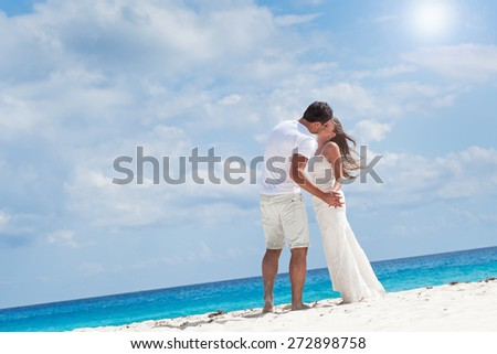 Beautiful young couple kissing on white sandy beach - stock photo