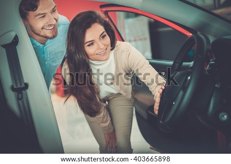 Beautiful young couple looking a new car at the dealership showroom.  - stock photo