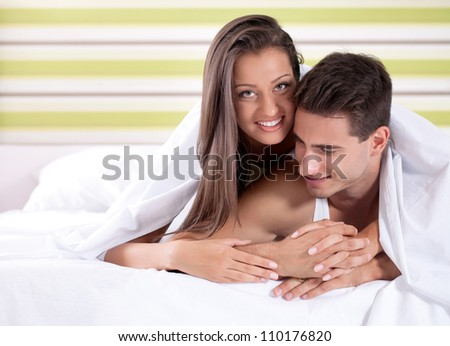 Beautiful young couple lying down under covers in bed, smiling and looking at camera. - stock photo