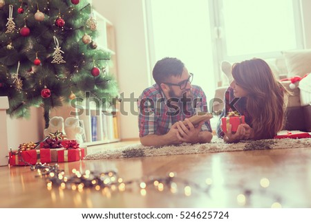 Beautiful young couple lying on the living room floor next to a nicely decorated Christmas tree, exchanging Christmas presents