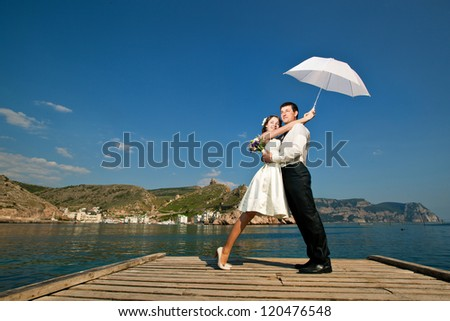 beautiful young couple male and female embracing by the sea in sunny summer day - stock photo