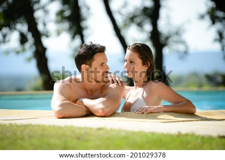 beautiful young couple man and woman on summer holiday in swimming pool resort - stock photo
