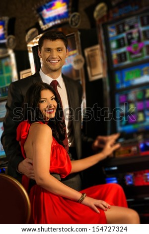 Beautiful young couple near slot machine in a casino - stock photo