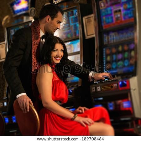Beautiful young couple near slot machine in a casino - stock photo