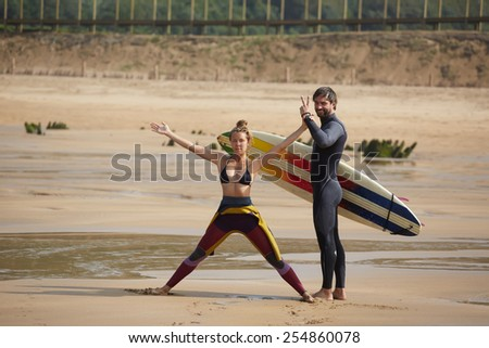 Beautiful young couple of surfers having fun standing on the beach at sunny day, girl and guy having fun during their summer vacation - stock photo