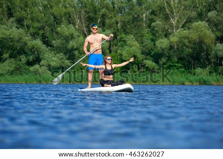 beautiful young couple  on vacation sport on stand up paddle board SUP, newlyweds man and woman, her arms