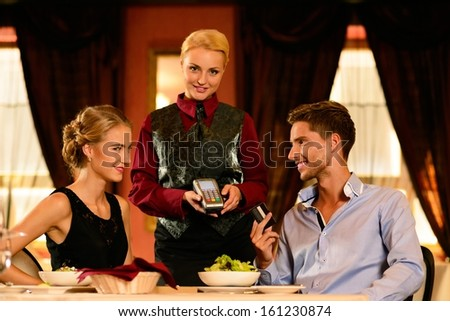 Beautiful young couple paying with card in a restaurant - stock photo
