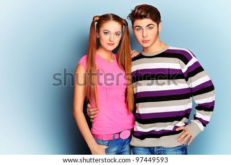 Beautiful young couple posing at studio over grey background.