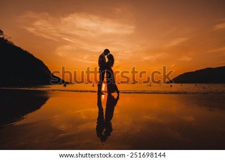 beautiful young couple posing at sunset in the sea - stock photo