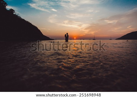 beautiful young couple posing at sunset in the sea