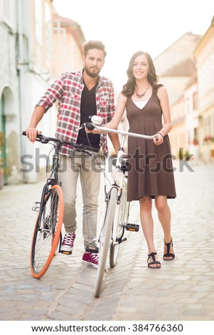 beautiful young couple posing beside bicycle on a street in a medieval town - stock photo