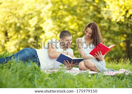 Beautiful young couple reading book in park - stock photo