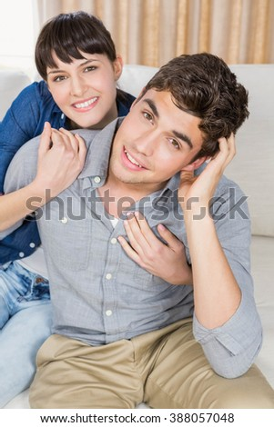 Beautiful young couple relaxing in a living room - stock photo