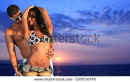 Beautiful young couple relaxing on the beach at sunset - stock photo