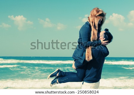 Beautiful young couple relaxing outdoor at winter beach - stock photo