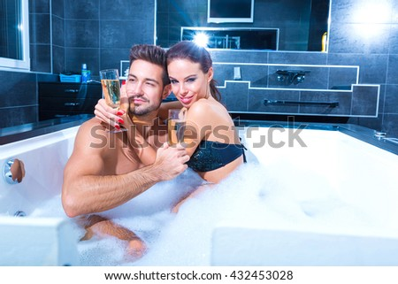 Beautiful young couple relaxing together and drinking Champagne in the Whirlpool. - stock photo
