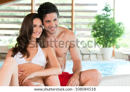 Beautiful young couple relaxing together at the edge of a swimmingpool at spa centre - stock photo