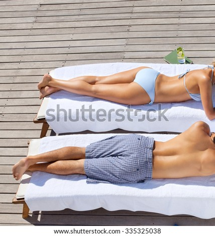 beautiful young couple resting in deck chairs  - stock photo