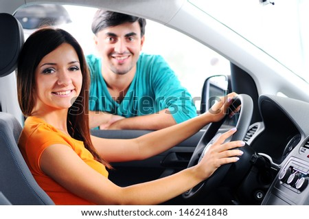 Beautiful young couple sitting at the front seats of their new car - stock photo