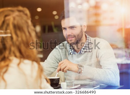 Beautiful young couple sitting in a cafe - stock photo