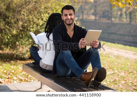 Beautiful Young Couple Sitting In The Park On A Beautiful Autumn Day - They Are Using Digital Tablet And Book - stock photo