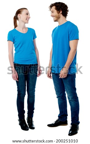Beautiful young couple standing and looking at each other - stock photo