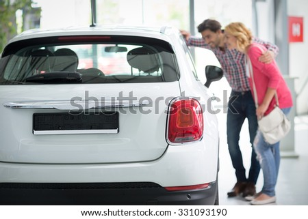 Beautiful young couple standing at the car dealership and making their decision, concept buy  new car  - stock photo