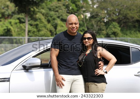 Beautiful young couple standing at their new car