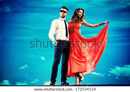 Beautiful young couple standing together outdoor over blue sky. - stock photo