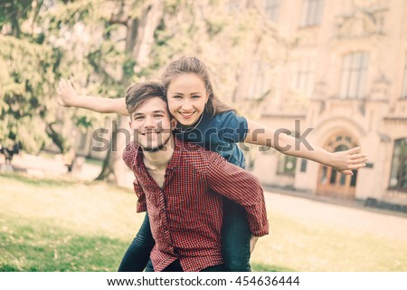Beautiful young couple travel. Fun time together.  Young caucasian man giving piggyback to his girl-friend.. Lifestyle concept - stock photo