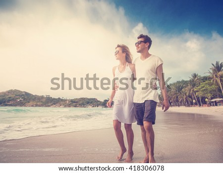 Beautiful young couple walking along the shore of a tropical sea. Vacation, honeymoon travel