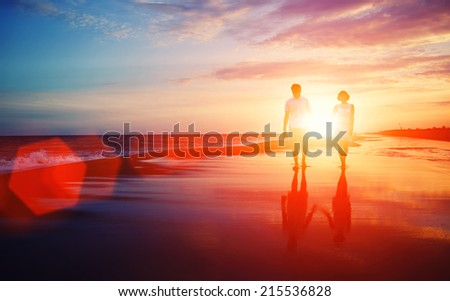 Beautiful young couple walking on a tropical beach at sunset, lovers or newlywed married young couple in romance on beautiful sunset at beach, young woman and man in love walking hand in hand on beach - stock photo