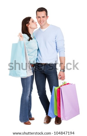 Beautiful young couple with shopping bags. Isolated on white
