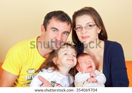 Beautiful young couple with their adorable children - stock photo