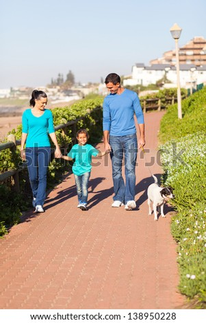 beautiful young couple with their daughter walking pet dog by seaside - stock photo