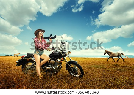 Beautiful young cowgirl carrying shotgun  while sitting on motorcycle - stock photo