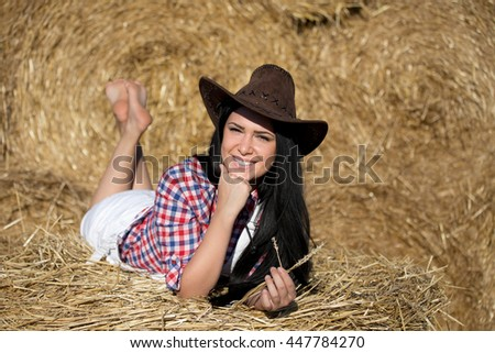 Beautiful young cowgirl with hat lying on stomach on straw pile and enjoying the moment - stock photo