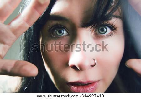Beautiful young curious girl looking through glass, closeup - stock photo