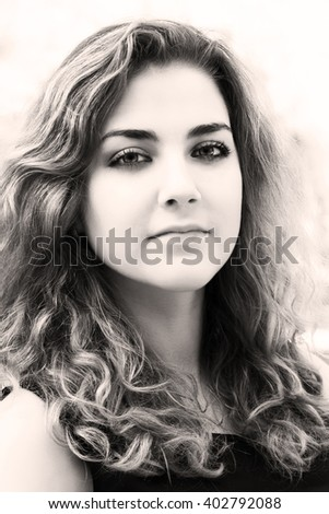 Beautiful young curly brunette. Close-up portrait in sepia tone