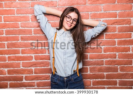 Beautiful young dark-haired girl in casual clothes posing and smiling, standing against brick wall - stock photo