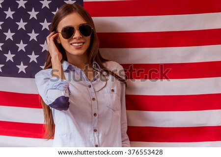 Beautiful young dark-haired girl in casual clothes with sunglasses posing and smiling, standing against American flag