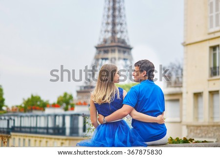 Beautiful young dating couple in Paris looking at the Eiffel tower